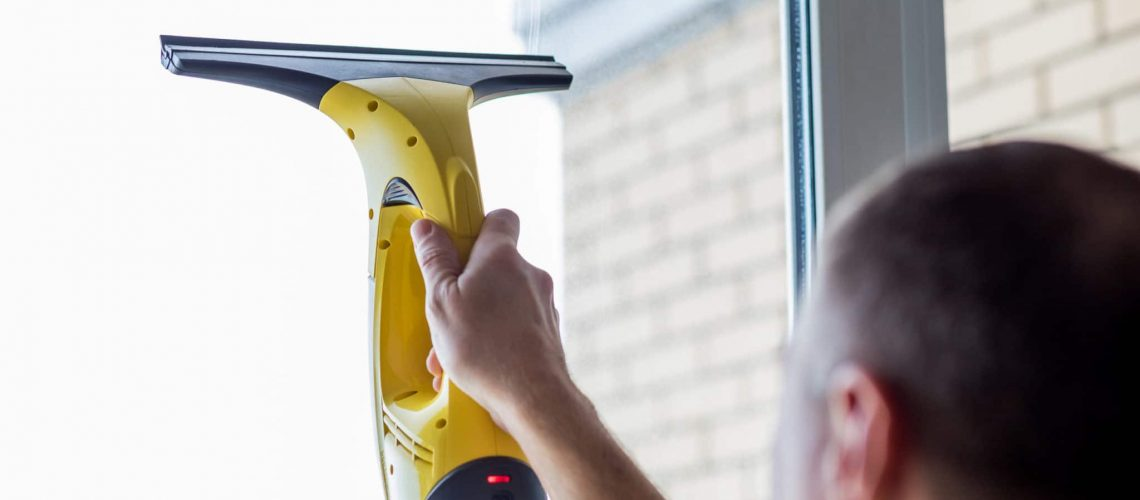 man-cleaning-windows-with-vacuum-cleaner-scaled